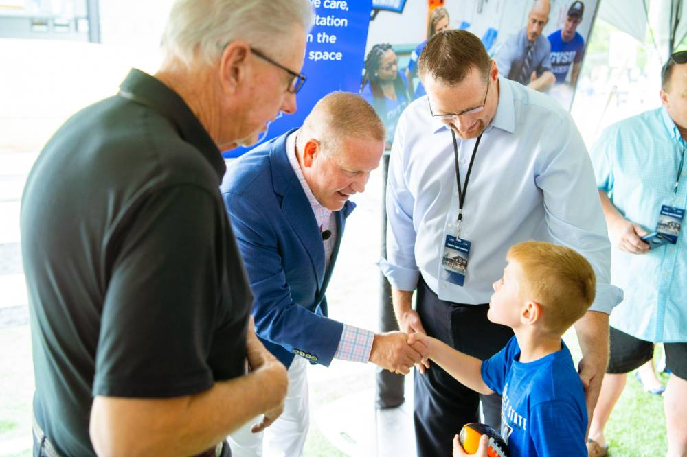 Brian Kelly shaking hands with a child at the Jamie Hosford Football Center dedication.